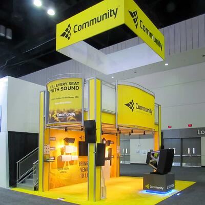Bright yellow two-story Community trade show booth at Infocomm